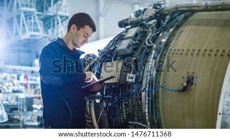 Aircraft Maintenance Mechanic Inspecting and Working on Airplane Jet Engine in Hangar #1476711368
