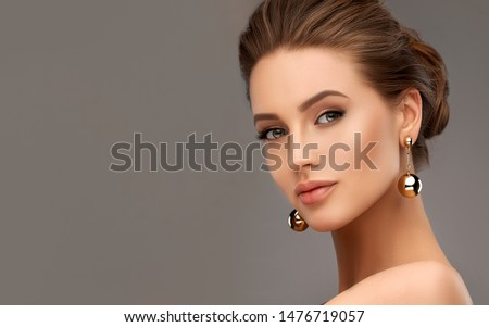 Beautiful girl . Fashionable and stylish woman in trendy jewelry big earrings .  Fashion look  , beauty and style. Natural makeup & easy styling Royalty-Free Stock Photo #1476719057