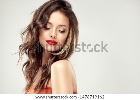 Beautiful  brunette model  girl  with long curly  hair . Hairstyle wavy curls . Red  lips and  nails manicure .    Fashion , beauty and make up portrait  Royalty-Free Stock Photo #1476719162