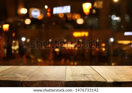 background Image of wooden table in front of abstract blurred restaurant lights #1476733142
