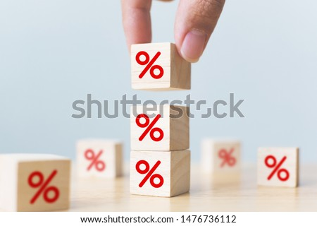 Interest rate financial and mortgage rates concept. Hand putting wood cube block increasing on top with icon percentage symbol upward direction #1476736112