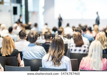 Business and entrepreneurship symposium. Speaker giving a talk at business meeting. Audience in conference hall. Rear view of unrecognized participant in audience. #1476787460