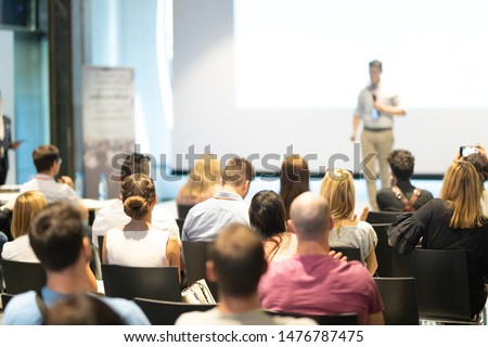 Male speaker giving a talk in conference hall at business event. Audience at the conference hall. Business and Entrepreneurship concept. Focus on unrecognizable people in audience. #1476787475