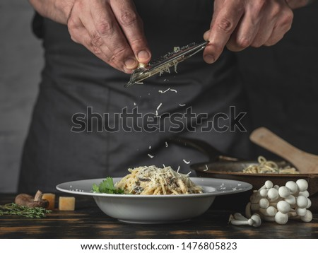 Chef hands cooking Italian pasta and adding cheese parmesan in dish on wooden table background. Royalty-Free Stock Photo #1476805823