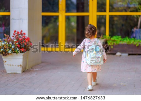 Curly cute little toddler girl back to school with holographic schoolbag or satchel, child going to kindergarten. Toddler kid first day at school or preschool. #1476827633