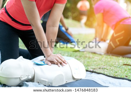 Asian female or runner woman training CPR demonstrating class in park by put hands and interlock finger over CPR doll give chest compression. First aid training for heart attack people or lifesaver. #1476848183