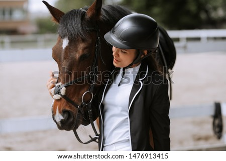 Beautiful professional female jockey standing near horse. woman horse rider is preparing to equitation. girl and horse. equestrian sport concept. riding horse vacation #1476913415