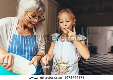 Senior woman in apron making batter for cake. Little girl tasting cake batter standing in kitchen with grandmother. #1476944873