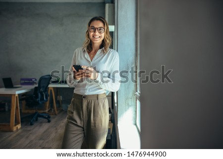 Smiling woman in casuals standing in office. Businesswoman with mobile phone in hand looking at camera. #1476944900