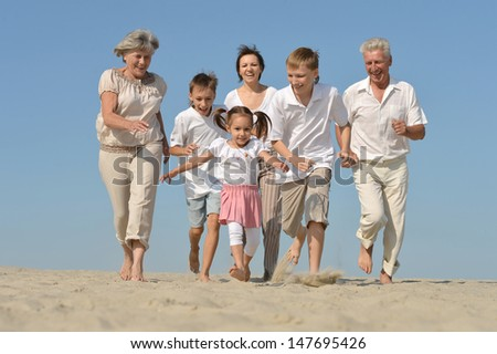 happy family playing catch-up on the sand in the summer #147695426