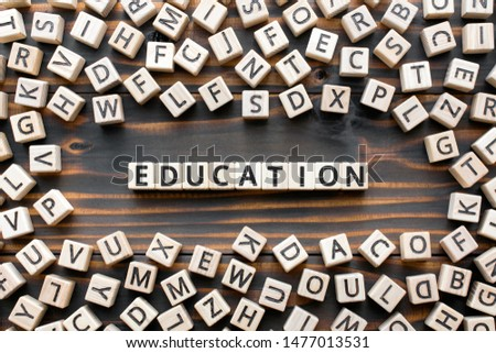 Education - word from wooden blocks with letters, school or college teaching or learning knowledge education  concept, random letters around, top view on wooden background #1477013531