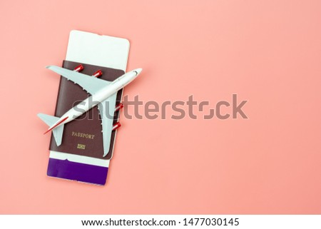 Table top view accessory of accessory travel in holiday background concept.Flat lay of airplane with passport and boarding pass ticket on modern rustic pink paper at home studio office desk.copy space #1477030145