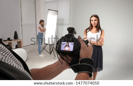 Professional photographer reviewing picture on camera and model with assistant in studio