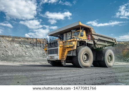 Large quarry dump truck. Transport industry. A mining truck is driving along a mountain road. Quarry truck carries coal mined. #1477081766