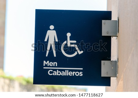 Illustrated sign with universal symbols indicating to fans where to locate the restrooms for men. #1477118627