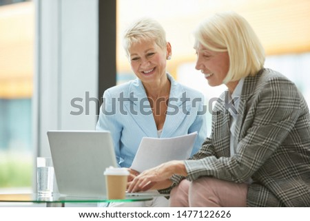 Two mature business partners watching online presentation on laptop and smiling while sitting on sofa at office #1477122626
