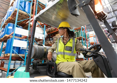 Low angle view of female staff driving forklift in warehouse. This is a freight transportation and distribution warehouse. Industrial and industrial workers concept #1477134242