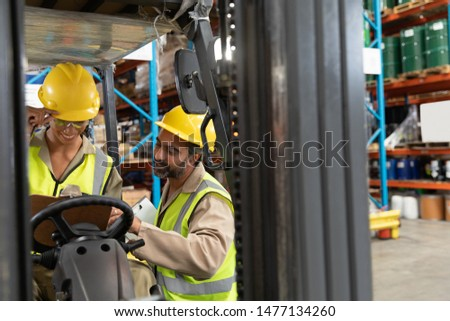 Multi-ethnic male and female staff discussing together over clipboard in warehouse. This is a freight transportation and distribution warehouse. Industrial and industrial workers concept #1477134260