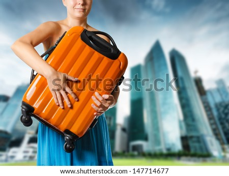 Woman in blue dress holds orange suitcase in hands. #147714677