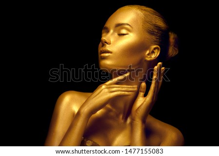 Fashion art Golden skin Woman face portrait closeup. Model girl with holiday golden Glamour shiny professional makeup. Gold jewellery, jewelry, accessories. Beauty gold metallic body, painted Skin #1477155083