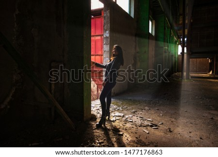 Foca, Bosna and Herzegovina, 03.10.2019. Young beautiful woman  in a dark room of abandoned factory #1477176863