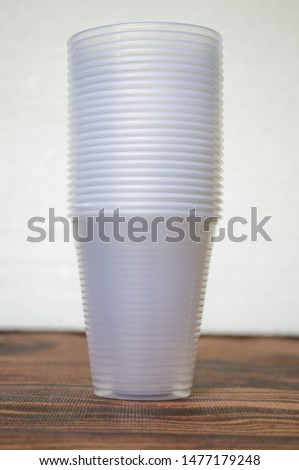 transparent disposable plastic cups on wooden table #1477179248