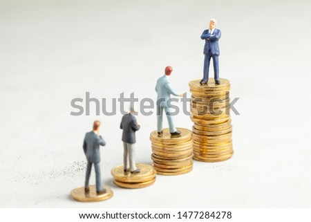 Successful businessman with big profits at the top of the stairs by coins and less successful businessmen with small companies. Adequate investment in the company #1477284278