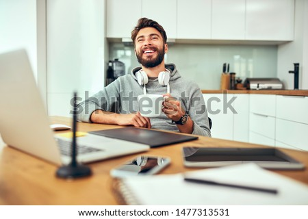 Young web developer laughing and drinking coffee while working from home office #1477313531
