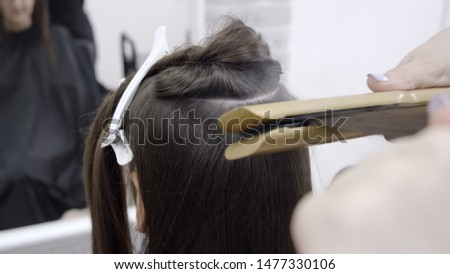hairdresser makes hair lamination in a beauty salon for a girl with brunette hair. hair care concept #1477330106