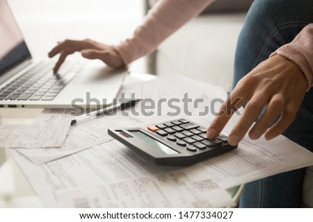 Close up cropped image young woman calculating monthly expenses, managing budget, entering data in computer application, sitting at table full of papers, loan documents, invoices, utility bills. Royalty-Free Stock Photo #1477334027