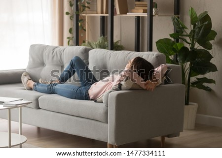 Young woman in casual clothes crossing hands behind head, sleeping on couch in modern cozy living room. Millennial lady relaxing, daydreaming, having rest at home on weekend. #1477334111