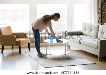 Millennial multiracial woman in casual clothes wiping dust from table in living room, using spray cleaner and rag, doing home cleaning routine, housekeeping specialist job concept. #1477334132