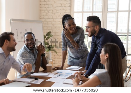 Happy friendly multiracial business team laughing working together at corporate briefing gathered at table, cheerful diverse office people group having fun talking enjoy teamwork during staff meeting Royalty-Free Stock Photo #1477336820