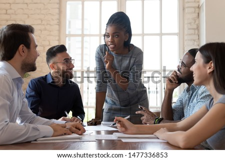Female black executive leader talking to happy diverse employees group at corporate office briefing, multiracial coworkers listening to african woman boss explain new strategy plan at team meeting Royalty-Free Stock Photo #1477336853