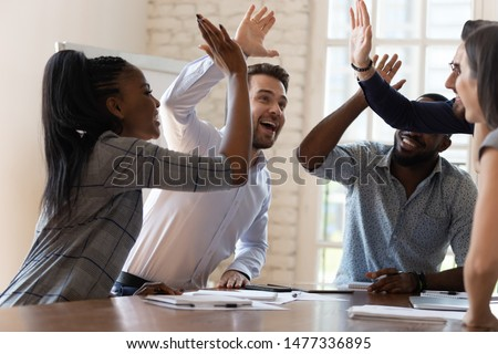 Multiracial euphoric business team people give high five at office table, happy excited diverse work group engaged in teambuilding celebrate corporate success win partnership power teamwork concept #1477336895
