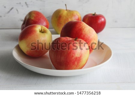 Fresh juicy apples in a white bowl on a light background. #1477356218