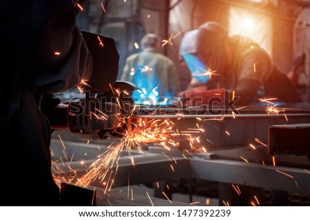 Worker polishes a metal surface with a grinder #1477392239
