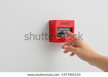 Woman using manual call point of fire alarm system #1477405514