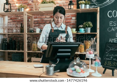 asian chinese woman rendering account with access point of sale terminal machine in coffee shop. elegant female waitress in apron holding note of customer order and touching on cash register in cafe #1477426196