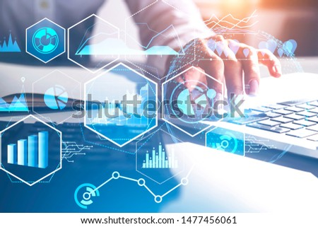Hand of woman in white typing on laptop in blurred office with double exposure of business infographics interface. Concept of market analysis and big data. Toned image #1477456061