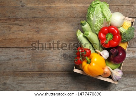 Fresh vegetables in crate on wooden background, top view. Space for text #1477470890