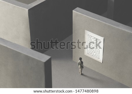 man lost in a complex maze, observing the map to find the way out;  surreal concept #1477480898