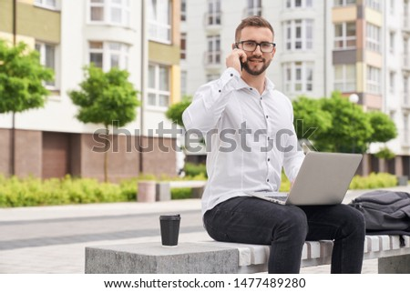 Young bearded man talking by phone, sitting on bench with laptop. Handsome, stylish freelancer in glasses looking at camera, posing on background of modern multistory houses. #1477489280