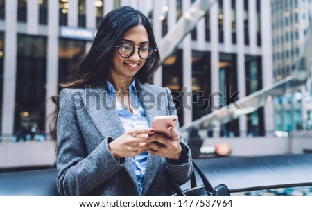 Elegant modern ethnic businesswoman in glasses and trendy coat standing on background of New York city street using mobile phone #1477537964