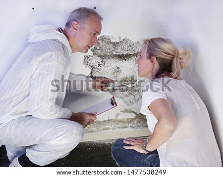a pest control contractor or exterminator with a blonde female customer at a mold destroyed wall and explain her the problem and the plan whats to do against mold pests and bugs for hygienic #1477538249