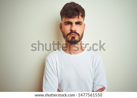 Young man with tattoo wearing t-shirt standing over isolated white background skeptic and nervous, disapproving expression on face with crossed arms. Negative person. #1477561550