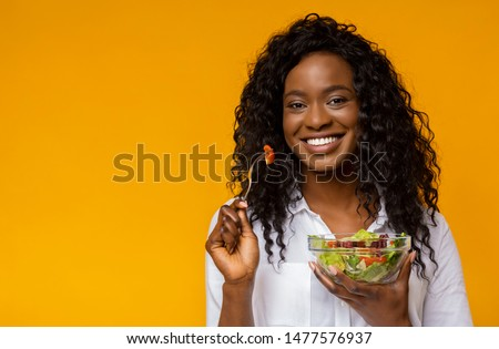 Healthy Nutrition. Happy African American Lady Eating Vegetable Salad, yellow studio background, copy space #1477576937