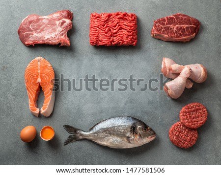 Carnivore or keto diet concept. Raw ingredients for zero carb or low carb diet - meat, poultry, fish, eggs and copy space in center on gray stone background. Top view or flat lay. Royalty-Free Stock Photo #1477581506