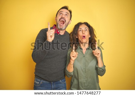 Beautiful middle age couple over isolated yellow background amazed and surprised looking up and pointing with fingers and raised arms. #1477648277