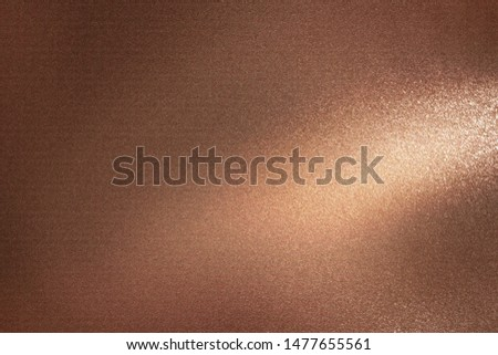 Glowing dark bronze metal wall with scratched surface, abstract texture background #1477655561
